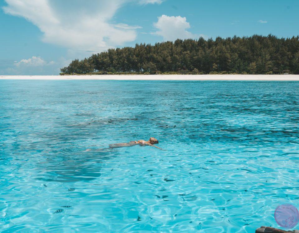 Mujer en una playa en Zanzibar con agua cristalina