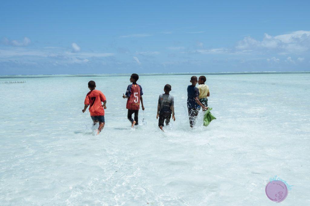 Consejos para viajar a Zanzibar - niños jugando en el agua en playa- Patoneando blog de viajes